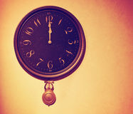 A vintage wall clock toned with a retro vintage instagram filter Stock Image