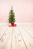 Vintage wall and wooden floor with Christmas tree. Vintage wall wooden floor and plinth with little Christmas tree and gifts royalty free stock images