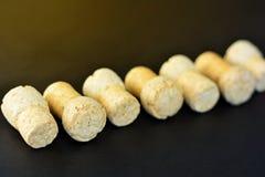 Diagonally lined seven sparkling wine corks on black background. Vintage warm lighted diagonal line of wine corks, focused one Stock Images