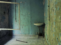 A vintage washbasin in the school corridor in Pripyat: blue walls with crumbling plaster, wires, cracked window frame without glas Royalty Free Stock Photos