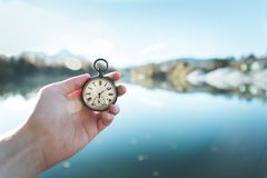 Vintage watch hand-held, autumwn view with lake and trees in the background. Hand held stop watch outdoors, autumn, blurry blue lake in the background time goes royalty free stock photos