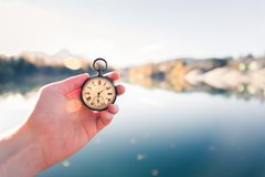 Vintage watch hand-held, autumwn view with lake and trees in the background. Hand held stop watch outdoors, autumn, blurry blue lake in the background time goes royalty free stock images