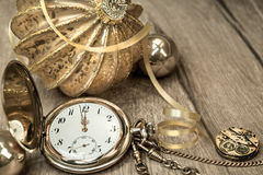 Vintage watch showing five to twelve and decorations on wood Royalty Free Stock Photos