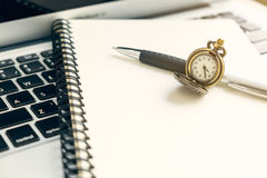 Vintage watch on spiral open notebook and pen on top of laptop Stock Photos