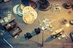 Vintage watchmakers workshop full of clocks and tools. On wooden table stock photography