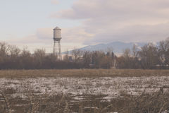 Vintage Water Tower with Mountains Stock Image