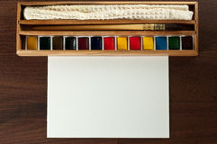 Vintage watercolor paint set with cloth, brush. Vintage watercolor paint with cloth, brush and blank paper on brown tabel. Top view royalty free stock photo
