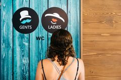 Vintage wc signs on wooden green door. Woman looking at vintage wc signs for Ladies and Gents on wooden green door. Concept choice royalty free stock photo