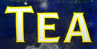 Vintage weathered 1920s enamelled tea sign. From an english tea room. Yellow and white text on a blue background Royalty Free Stock Photo