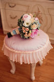 Vintage wedding bouquet in bodoir interior. Vintage wedding bouquet om the pink chair Royalty Free Stock Image
