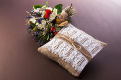 Vintage wedding pillow with ring and bouquet Royalty Free Stock Photos