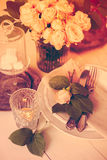 Vintage wedding table decorations with roses, candles  cutlery Royalty Free Stock Photo