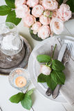 Vintage wedding table decorations with roses, candles  cutlery Royalty Free Stock Photos