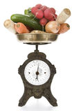 Vintage weight scale with vegetables. Heap of vegetables on old-fashioned kitchen scale isolated on white. Clipping path incl Stock Images