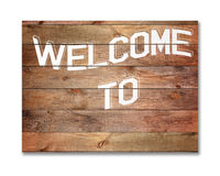 Vintage WELCOME sign on natural wooden surface. Vintage WELCOME sign on natural wooden surface isolated on white background. Closeup Royalty Free Stock Photo