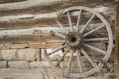Vintage wheel weeds log and stone wall Stock Photography