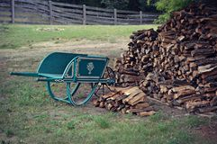 Vintage Wheelbarrow and Woodpile Royalty Free Stock Photos