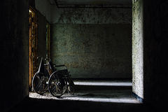 Vintage Wheelchair in Hallway - Abandoned Hospital / Sanitarium - New York. An interior view of a vintage wheelchair in a hallway inside an abandoned hospital in royalty free stock image