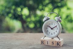 Vintage White Alarm Clock placed on wood word RISK. The concept of risk diversification of a business or organization. For the. Unexpected. as background stock photography