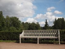 Vintage white bench in the Park. On the background of trimmed bushes, trees and cloudy sky stock photo