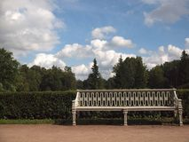 Vintage white bench in the Park. On the background of trimmed bushes, trees and cloudy sky royalty free stock images