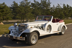 Vintage white car. A white vintage cabriolet on a road, sunny day Royalty Free Stock Images