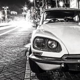 Vintage white car parked in center of Amsterdam at night time. Black-white photo.  Stock Photo