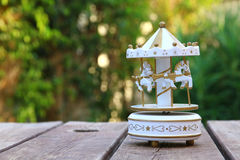 Vintage white carousel horses over wooden table outdoors Stock Photo