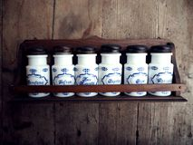 Vintage white ceramic storage jars, used for spices on rustic wood background. Every jar has the name of a spice in italian. Vintage white ceramic storage jars Stock Photography