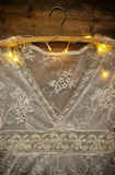 Vintage white crochet lace top on hanger with garland lights on wooden background Royalty Free Stock Images