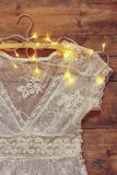 Vintage white crochet lace top on hanger with garland lights on wooden background Royalty Free Stock Photography