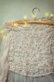 Vintage white crochet lace top on hanger with garland lights on wooden background Royalty Free Stock Photo
