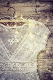 Vintage white crochet lace top on hanger with garland lights on wooden background Stock Image