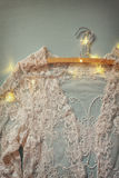 Vintage white crochet lace top on hanger with garland lights  Stock Image
