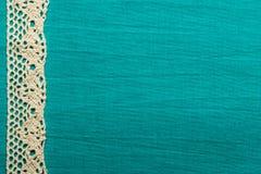 Vintage white lace over blue background. Retro border for invitations celebration. Vintage white lace over green blue textile background stock photo