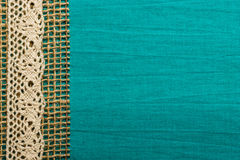 Vintage white lace over blue background. Retro border or rustic style frame. Vintage white lace and burlap string over green blue textile background royalty free stock images