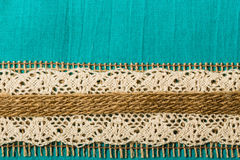 Vintage white lace over blue background. Retro border or rustic style frame. Vintage white lace and burlap string over green blue textile background royalty free stock photography