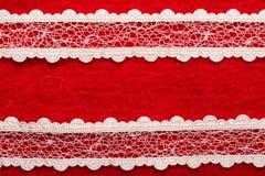Vintage white lace over red background. Retro border for invitations celebration. Vintage white lace over red textile background stock photos