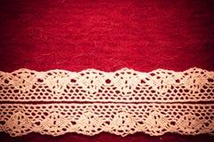 Vintage white lace over red background. Retro border for invitations celebration. Vintage white lace over red textile background royalty free stock images