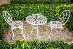 Vintage white metal table and chairs in garden Stock Image