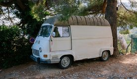 Vintage white van minibus on a gravel road under a tree royalty free stock images