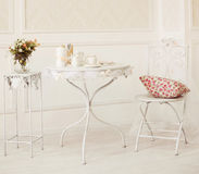 Vintage white room with chair and table with flowers pillow, coffee cups and candles Royalty Free Stock Photos