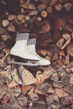 Vintage white skates on wood stack. A pair of vintage white skates on stack of firewood Stock Images