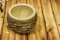 Vintage wicker beige ceramic pot on wooden background Stock Photo