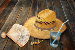 Vintage wicker hat, folding fan and cold drink on wooden table Royalty Free Stock Image