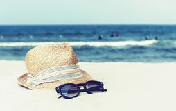 Vintage wicker straw hat and black sun glasses on a tropical beach, summer concept royalty free stock photography