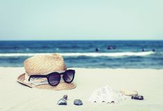 Vintage wicker straw hat and black sun glasses on a tropical beach, summer concept stock image