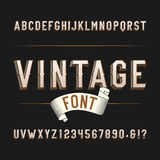 Vintage wild west alphabet font. Distressed effect letters and numbers on a dark background. Stock Photos