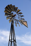 Vintage Windmill. Vertical shot of an old metal windmill against a blue sky with wispy clouds Royalty Free Stock Photography