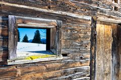 Vintage window and door of old wooden cabin mirrors winter mountain landscape. Wooden rustic background. Royalty Free Stock Photography